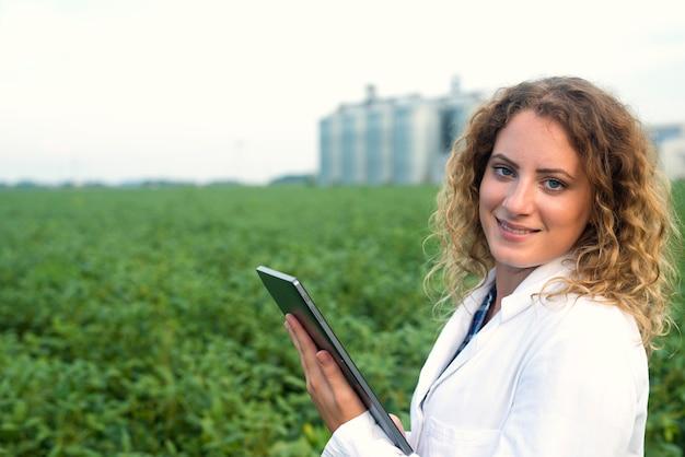 Vrouwelijke landbouwingenieur met tablet op veld Gratis Foto