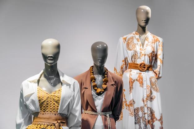 Vrouwelijke ledenpoppen die zich in de vertoning van het opslagvenster bevinden van winkel van de vrouwen de toevallige kleding in winkelcomplex Premium Foto