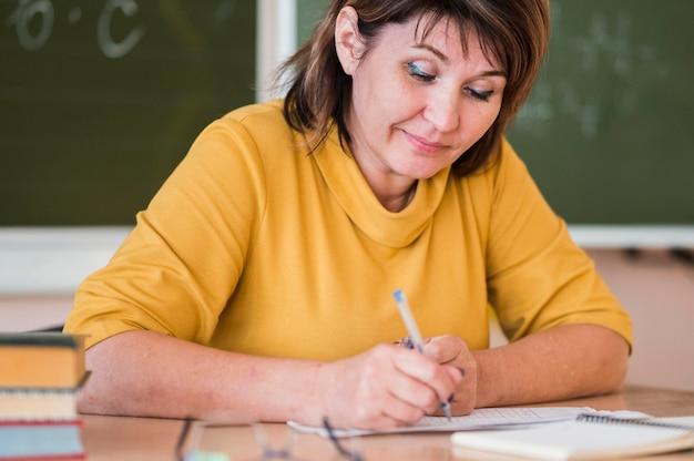 Vrouwelijke leraar aan het bureau dat aantekeningen maakt Gratis Foto