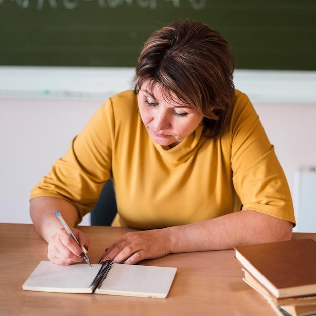 Vrouwelijke leraar bij bureau het schrijven Gratis Foto