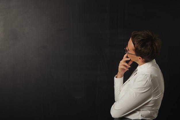 Vrouwelijke leraar die een leeg zwart bord bekijkt Gratis Foto