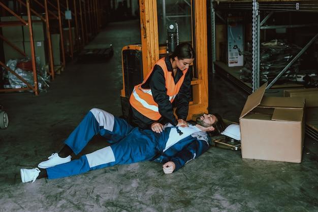 Vrouwelijke magazijnmedewerker die eerste hulp biedt aan de mens Premium Foto