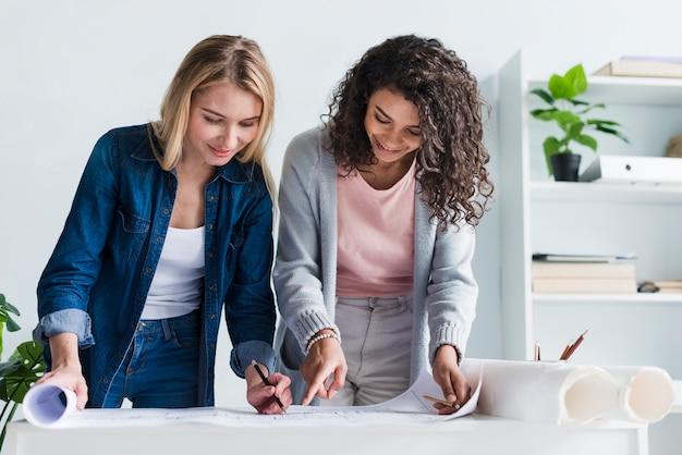 Vrouwelijke medewerkers die over de tekening van het document vloerplan leunen Gratis Foto