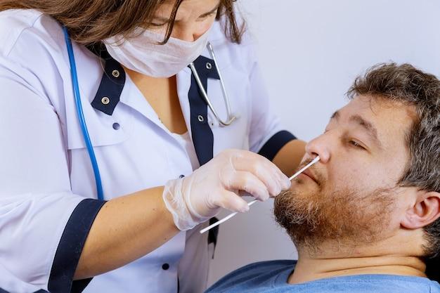 Vrouwelijke medische werker neemt een uitstrijkje voor coronavirus-monstertest van een mogelijk geïnfecteerde man met chirurgische gezichtsmaskers personeel neemt een neusmonster Premium Foto