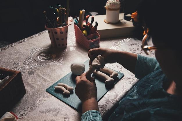 Vrouwelijke meester die sculptuur maakt van klei Gratis Foto