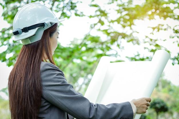 Vrouwelijke milieu-ingenieur draagt een pak, draagt een witte hoed, staande houden een papieren plan Premium Foto