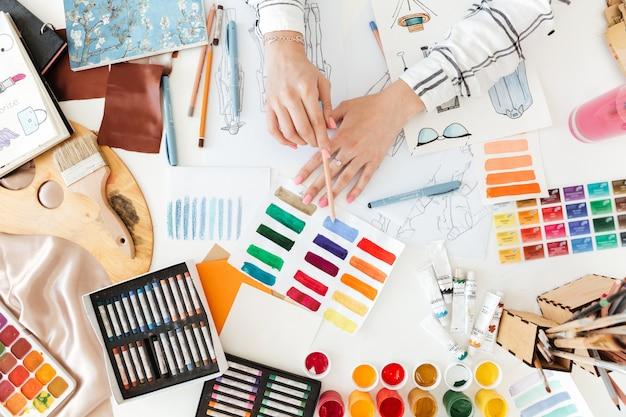 Vrouwelijke modeontwerper bezig met schetsen met verf Gratis Foto