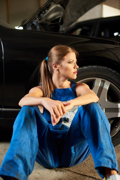 Vrouwelijke monteur kijkt in de verte zitten in de buurt van de zwarte auto. Premium Foto