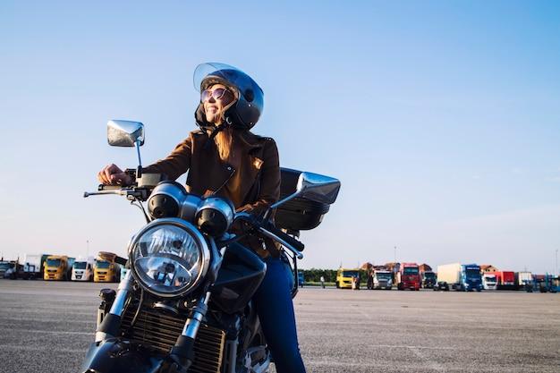 Vrouwelijke motorrijder in leren jas en helm zittend op retro motor en glimlachen Gratis Foto