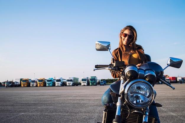 Vrouwelijke motorrijder in leren jas zittend op retro motor en glimlachen Gratis Foto