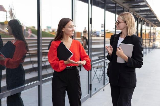 Vrouwelijke ondernemers die gebarentaal buitenshuis gebruiken Gratis Foto