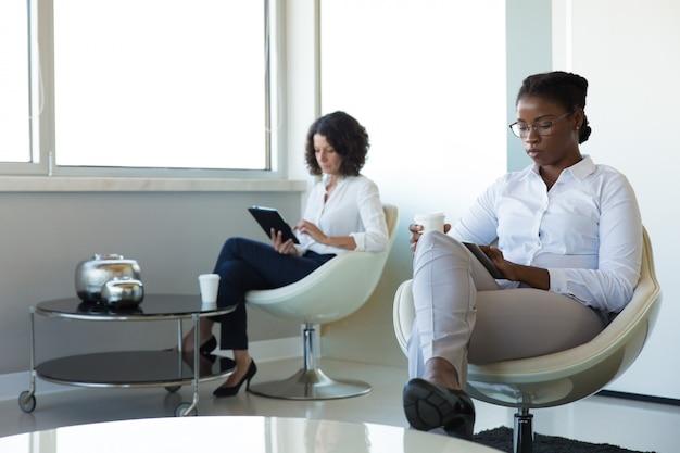 Vrouwelijke ondernemers genieten van werk pauze in office lounge Gratis Foto