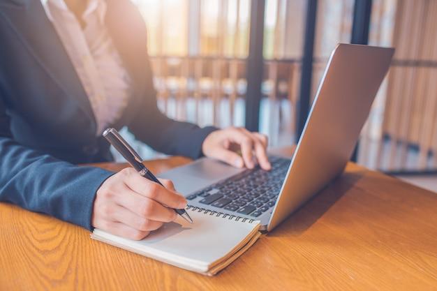 Vrouwelijke ondernemers maken aantekeningen op papier met een zwarte pen en ze gebruikt een laptop op een houten bureau op kantoor. Premium Foto