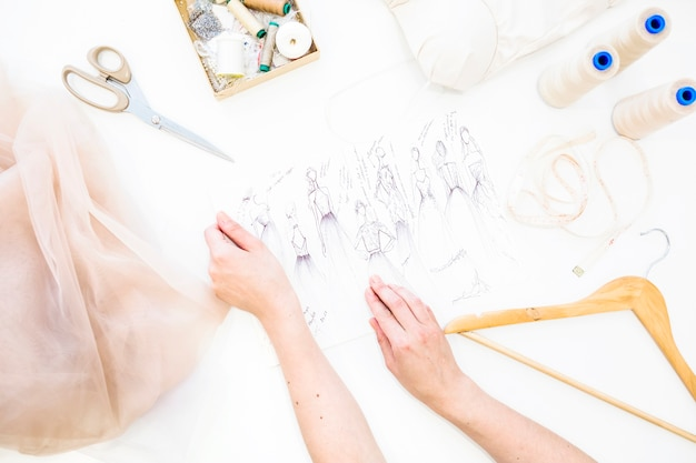 Vrouwelijke ontwerper hand met mode schets over bureau Gratis Foto