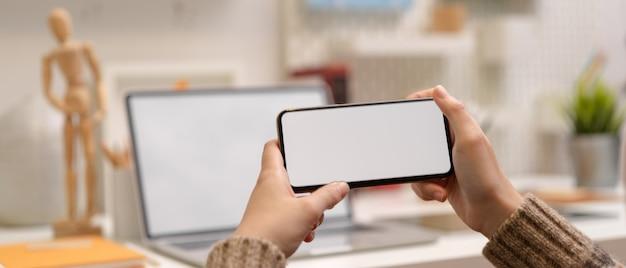 Vrouwelijke ontwerper neemt een pauze en kijkt naar video op horizontale mock-up smartphone terwijl hij aan de werktafel zit Premium Foto