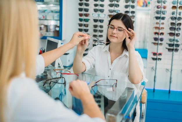 Vrouwelijke opticien en consument kiest brilmontuur in optica winkel. selectie van brillen met professionele optometrist Premium Foto