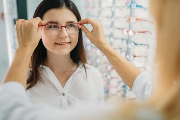 Vrouwelijke opticien en klant kiest brilmontuur tegen showcase met brillen in optica winkel. selectie van brillen met professionele optometrist Premium Foto