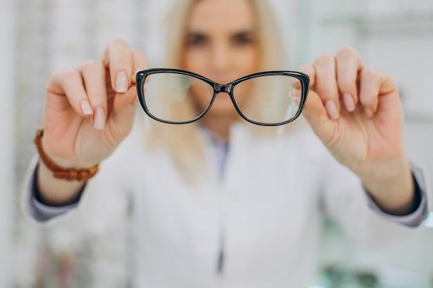 Vrouwelijke opticien werken bij optische winkel Gratis Foto