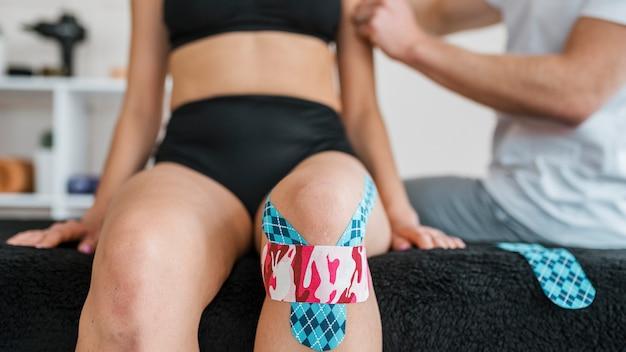 Vrouwelijke patiënt bij fysiotherapie met kniebrace tape Gratis Foto