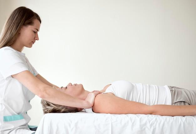 Vrouwelijke patiënt die therapie ondergaat met een fysiotherapeut Gratis Foto