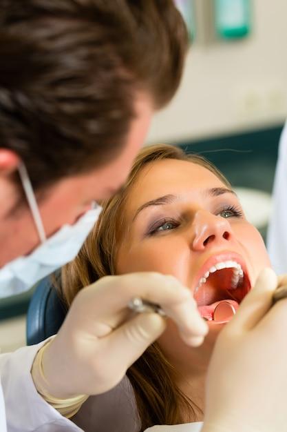 Vrouwelijke patiënt met dentista tandheelkundige behandeling, maskers en handschoenen dragen Premium Foto