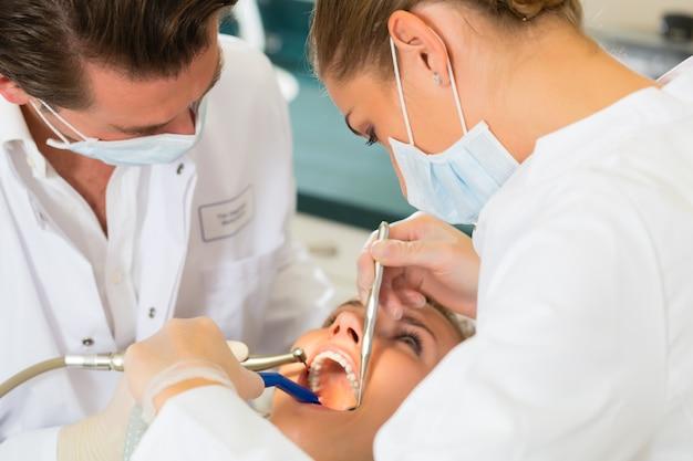 Vrouwelijke patiënt met tandarts en assistanta tandheelkundige behandeling, maskers en handschoenen dragen Premium Foto