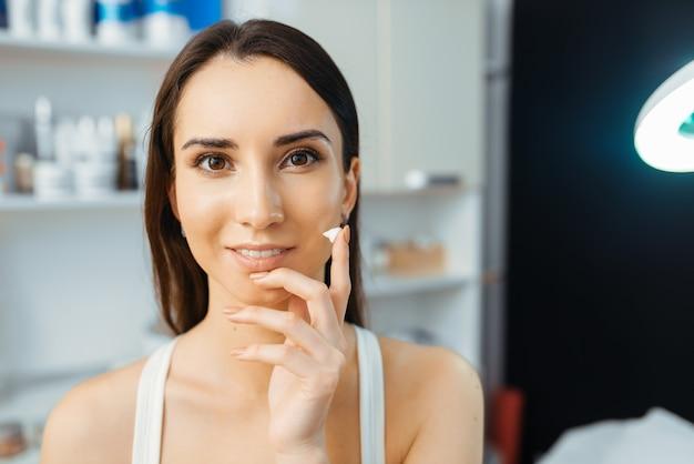 Vrouwelijke patiënt toont crème op vinger in schoonheidsspecialist kantoor. verjongingsprocedure in schoonheidsspecialiste salon. Premium Foto
