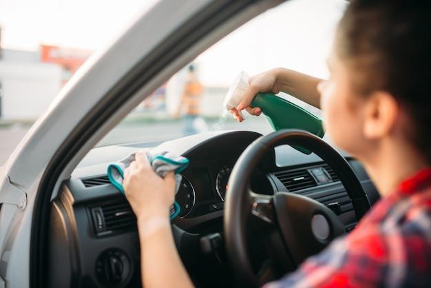 Vrouwelijke persoon poetst het dashboard van de auto Premium Foto