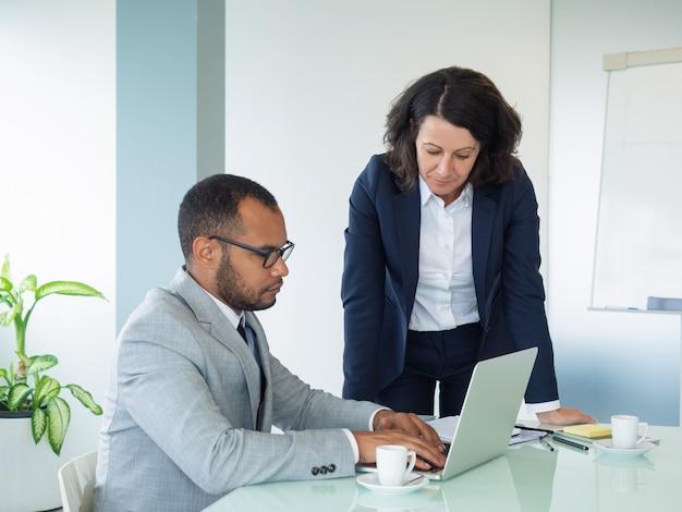 Vrouwelijke professional die nieuwe werknemer helpt Gratis Foto
