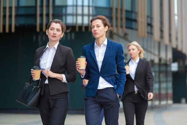 Vrouwelijke professionals met papieren koffiekopjes dragen kantoorpakken, samen wandelen in de stad, praten, project bespreken of chatten. vooraanzicht. zakenvrouwen buitenshuis concept Gratis Foto