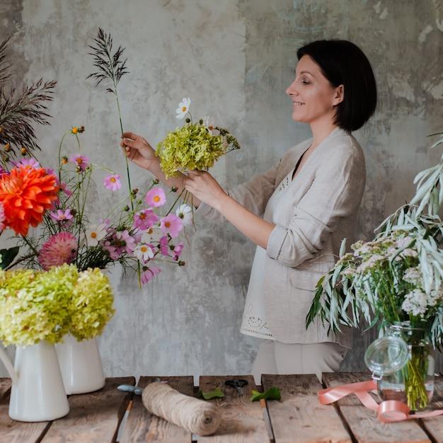 Vrouwelijke professionele bloemist bereidt de opstelling van wilde bloemen voor. Premium Foto