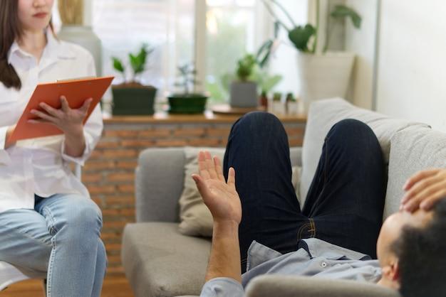 Vrouwelijke professionele psycholoog die een overleg leidt aan zware mannelijke patiënt op bank. Premium Foto