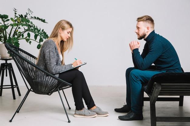 Vrouwelijke psycholoog die aan gedeprimeerde mannelijke patiënt luisteren en nota's over klembord neerschrijven Premium Foto