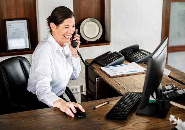 Vrouwelijke receptioniste die bij de receptie werkt Gratis Foto