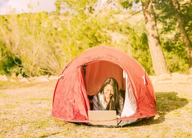 Vrouwelijke reiziger die met laptop in het kamperen werkt Gratis Foto