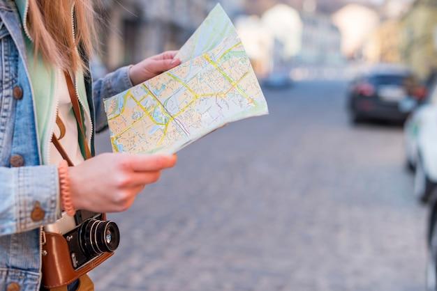 Vrouwelijke reiziger die richting op locatiekaart zoeken in stadscentrum Gratis Foto