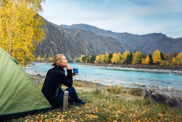 Vrouwelijke reiziger zittend op gras in de buurt van de tent, koffie drinken uit thermosflessen en het prachtige uitzicht op de rivier en de bergen bewonderen. ochtend vrouw toerist, plezier in de reis Premium Foto