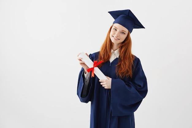 Vrouwelijke roodharige afgestudeerde student met diploma glimlachen. copyspace. Gratis Foto