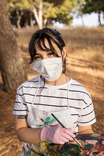 Vrouwelijke schilder buitenshuis met medisch masker Gratis Foto