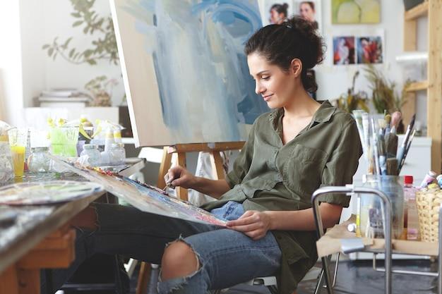 Vrouwelijke schilder in haar kunstatelier Gratis Foto