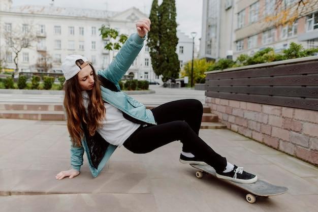 Vrouwelijke skater beoefenen van skateboarden buitenshuis Premium Foto