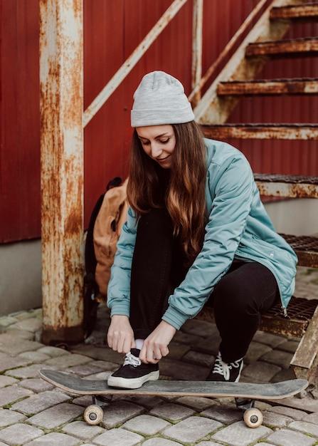 Vrouwelijke skater zit naast haar skateboarden buitenshuis Gratis Foto