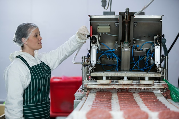 Vrouwelijke slager die hamburgerpasteitje verwerkt Premium Foto