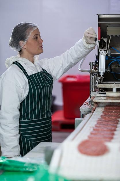 Vrouwelijke slager die hamburgerpasteitjes verwerkt Premium Foto