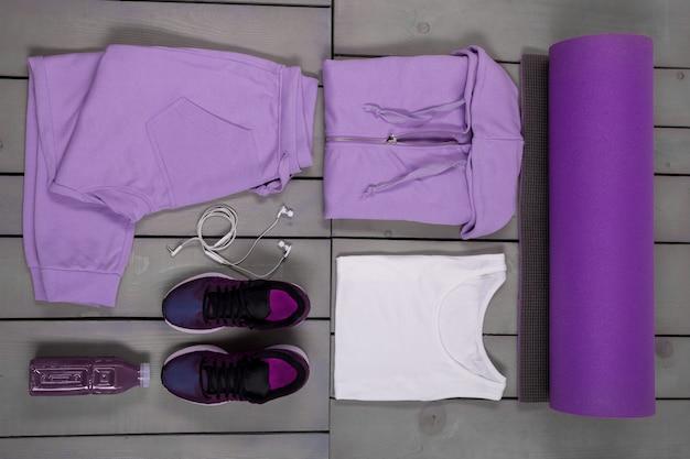 Vrouwelijke sportartikelen. paarse sportbroek, schoenen, pak, mat, witte hoofdtelefoon met waterfles Premium Foto