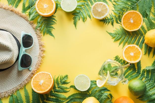Vrouwelijke strandstro sunhat, zonnebril, citrics op geel. Premium Foto