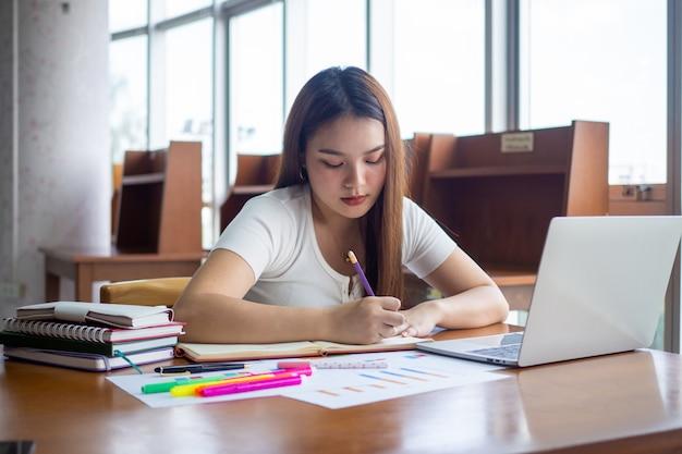 Vrouwelijke studenten zitten en maken huiswerk maak aantekeningen, maak rapporten in de bibliotheek. Premium Foto