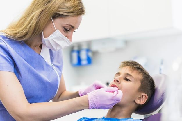 Vrouwelijke tandarts die de tanden van de kindpatiënt in kliniek onderzoeken Gratis Foto