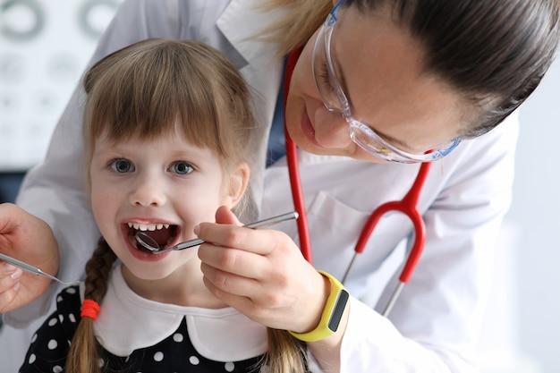 Vrouwelijke tandarts kijkt naar open mond weinig gelukkig meisje Premium Foto