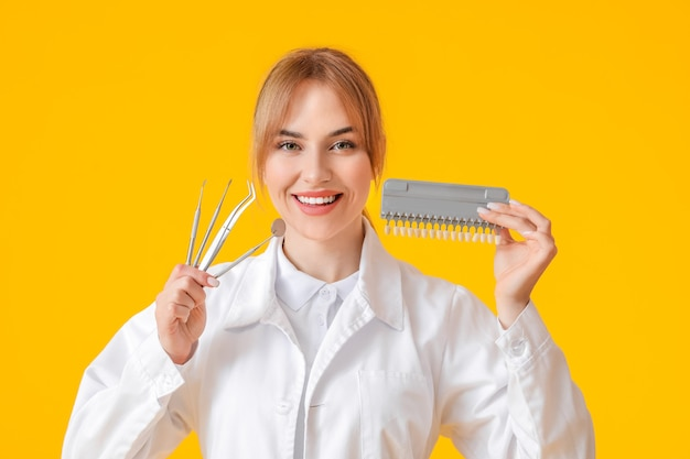 Vrouwelijke tandarts met tools en tanden kleurenkaart op geel oppervlak Premium Foto